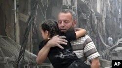 Seorang pria menggendong seorang anak perempuan menyusul serangan udara di Aleppo, Suriah (28/4).