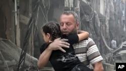 یک مرد در حلب کودکی را پس از یک حمله هوایی حمل می کند.