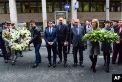 Thủ tướng Pháp Manuel Valls (ở giữa, bên trái), Thủ tướng Bỉ Charles Michel (giữa) và Chủ tịch Ủy ban châu Âu Jean-Claude Juncker (ở giữa, bên phải) đặt vòng hoa tại ga điện ngầm Maelbeek ở Brussels ngày 23/3/2016.