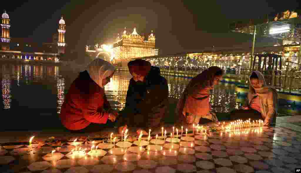 Sikh devotees light candles in the pre-dawn hours at the illuminated Golden Temple, the holiest of Sikh shrines, during the birth anniversary of Guru Nanak, the first Sikh Guru, in Amritsar, India.