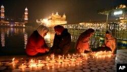 Sejumlah umat Sikh menyalakan lilin di Kuil Emas di Amritsar, India, 30 November 2020.