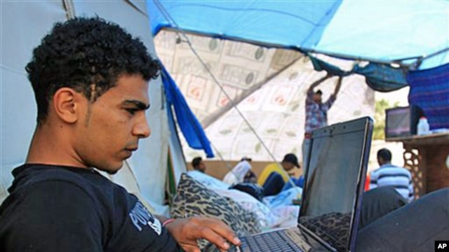 A Bahraini anti-government protester works on his computer in a tent at Pearl roundabout in Manama, Bahrain, February 28, 2011