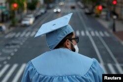 Seorang lulusan program pascasarjana dari Universitas Columbia tampak di kampusnya seehari sebelum upacara wisuda, yang akan diadakan secara daring karena wabah virus corona (Covid-19) di Manhattan, New York, 15 Mei 2020. (Foto: Reuters)