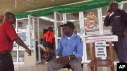 """지난 1월 라이베이라 몬로비아의 정부 청사 출입구에서 보건 관계자가 통행하는 사람들의 에볼라 감염 여부를 검사하기 위해 체온을 재고 있다. 그 옆에는 """"건물을 들어가기 전에 손을 씻어주세요"""" 라는 안내문이 붙어있다."""