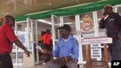 Seorang petugas kesehatan (tengah) memeriksa suhu badan seorang sebelum memasuki gedung pemerintahan di Monrovia, Liberia (Foto: dok).
