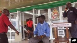 """Un homme se fait prélever la température d'être autorisé à entrer dans un bâtiment du gouvernement, où un message, à droite, indique """"veuillez laver vos mains avant d'entrer dans"""" le bâtiment à Monrovia, Libéria, le 14 janvier 2016."""