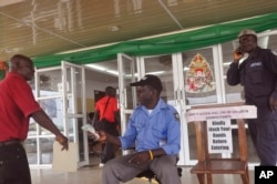 """A health worker takes a man's temperature, center, before his is allowed to enter into a government building, with a message, right, reading """"Kindly wash your hands before entering"""" the building in Monrovia, Liberia, Jan. 14, 2016."""