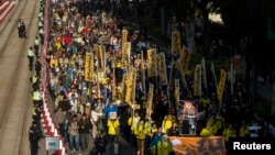 Thousands of pro-democracy protesters march in the streets to demand universal suffrage and urge Hong Kong's Chief Executive Leung Chun-ying to step down in Hong Kong, Jan. 1, 2014.