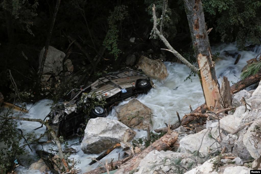 2017年8月10日,中国四川省九寨沟附近的地震和泥石流后,一辆汽车翻在一条小路旁边的一条小溪里。