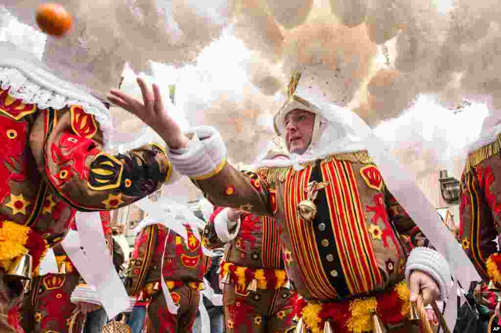 A 'Gilles of Binche' throws an orange during the Binche carnival, in Binche, Belgium. The Carnival of Binche is recognized by Unesco as a masterpiece of the Oral and Intangible Heritage of Humanity.