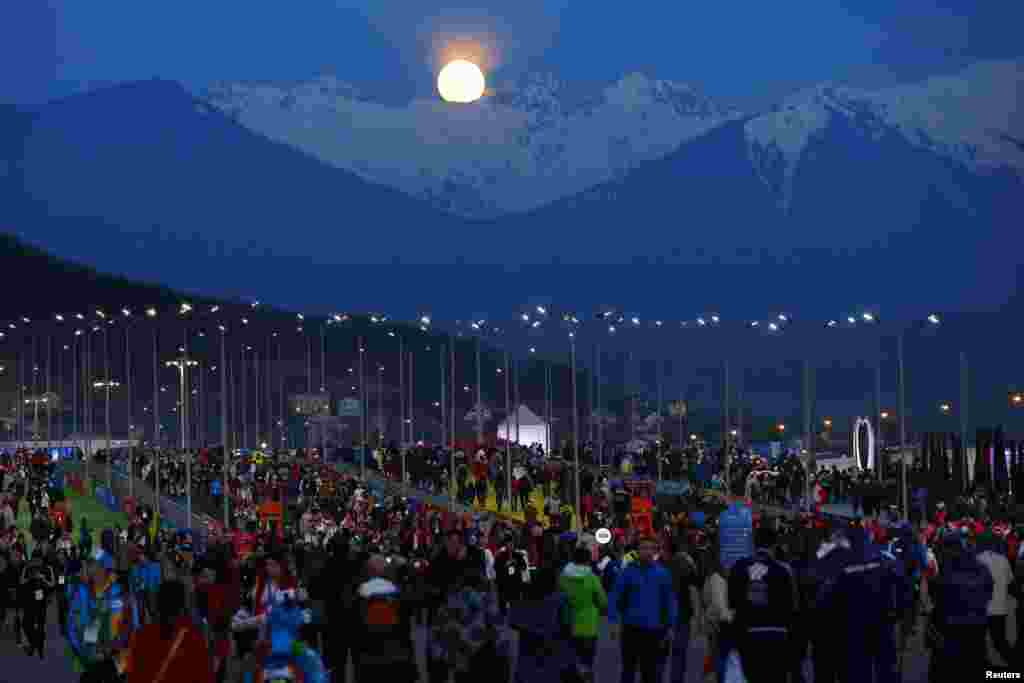 The moon rises over the mountains behind the public entrance to the Olympic Park at the 2014 Sochi Winter Olympics in Russia.