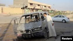 2013年8月23日在伊拉克首都巴格達北部一個城鎮發生汽車炸彈爆炸的現場。