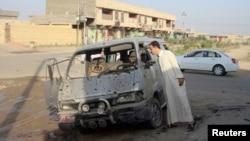 Seorang warga memeriksa sebuah kendaraan yang hancur sehari setelah serangan bom di Dujail, 50 kilometer sebelah utara Baghdad, 23 Agustus 2013.