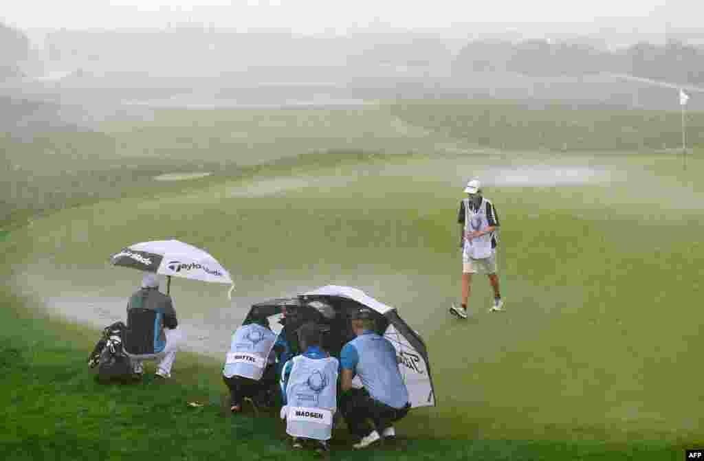 포르투갈 남부 빌라모우라에서 열린 골프대회에서 출전 선수와 캐디들이 우산 아래서 소나기를 피하고 있다.