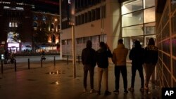Unaccompanied minors from Morocco seeking shelter, stand outside a police station in Barcelona, Spain, Nov. 9, 2018.