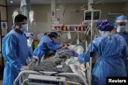 Nurses wearing protective suits, prepare a patient with coronavirus disease (COVID-19) to be transferred to Masih Daneshvari Hospital, in Tehran, Iran March 30, 2020. WANA (West Asia News Agency)/Ali Khara via REUTERSکرونا ایران