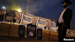 An ultra-Orthodox Jew stands near Shas campaign banners that depict party leader Aryeh Deri (top) and near pictures of Rabbi Yisrael Abuhatzeira during an annual pilgrimage to the Rabbi's gravesite in the southern town of Netivot, Israel, Jan. 14, 2013.