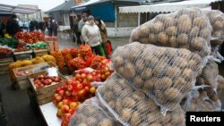 FILE - People walk past goods at the market in Suwalki, Poland.