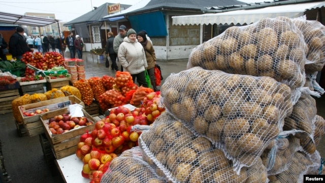 FILE - People walk past goods at the market in Suwalki, Poland, March 2009.