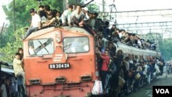 Penumpang bergelantungan di salah satu kereta api yang bergerak keluar dari stasiun Tanah Abang, Jakarta pada saat mudik lebaran (foto: dok).