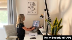 In this photo provided by Kelly Soderlund, Kelly is working remotely from her home in Walnut Creek, Calif., Thursday, Sept. 2, 2021. Changing to a mix of in-home and in-office work is perfect for people like Kelly Soderlund, a mother of two young children who works in offices in San Francisco and Palo Alto, California, for TripActions. (Kelly Soderlund via AP)