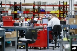 In this Oct. 24, 2017, photo, an employee wears his laboratory coat at his workstation at Lord Corporation, a manufacturer of industrial coatings, adhesives, bearings, and sensing equipment for range of commercial markets