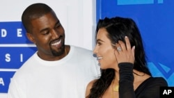 FILE - In this Aug. 28, 2016 file photo, Kanye West, left, and Kim Kardashian West arrive at the MTV Video Music Awards in New York.