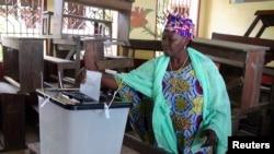 一名女子9月28日在几内亚首都科纳克里的投票站投票