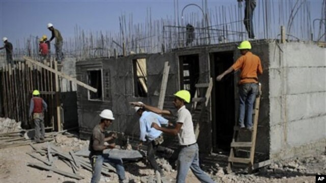 Palestinian men work on a construction site in the West Bank Jewish settlement of Kiryat Arba, near Hebron, 20 Oct 2010