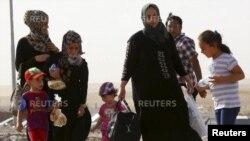 Một gia đình chạy trốn bạo lực tại thành phố Mosul, ngày 11/6/2014.
