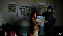 یوه افغانه ښوونکې په افغانستان کې د ماینونو د مختلفو ډولونو په هکله د خبرتیا او معلوماتو ورکولو په حال کې