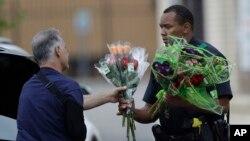 Seorang polisi di Dallas, Texas menerima bunga tanda simpati dari seorang warga, pasca insiden penembakan polisi di sana (9/7).