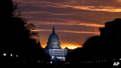 FILE - The U.S. Capitol Building is illuminated during sunrise in Washington.