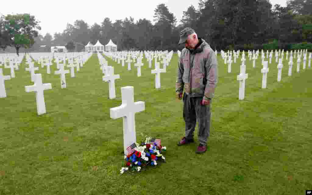 Paul Clifford, 70, from Boston, Massachusetts, stands after placing flowers on a grave in the Normandy American Cemetery and Memorial, in Colleville sur Mer, France, June 4, 2014.