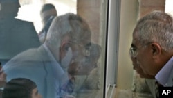 Palestinian Prime Minister Salam Fayyad, right, looks through a window into a classroom as he visits a school in the West Bank village of Dahiat Al-Barid on the outskirts of Jerusalem, Tuesday, Nov. 2, 2010.