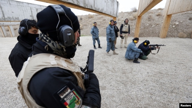 A German police officer guards an Afghan National Police trainee as she fires her weapon at a training center in Mazar-e-Sharif, northern Afghanistan, December 18, 2012.