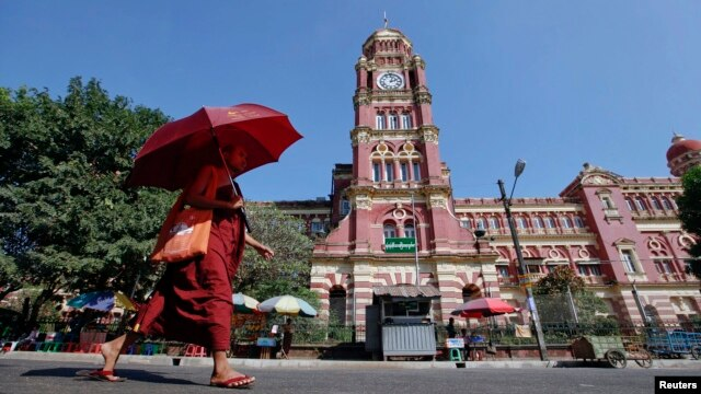 FILE - A Buddhist monk walks near the High Court in Rangoon, Nov. 26, 2011.