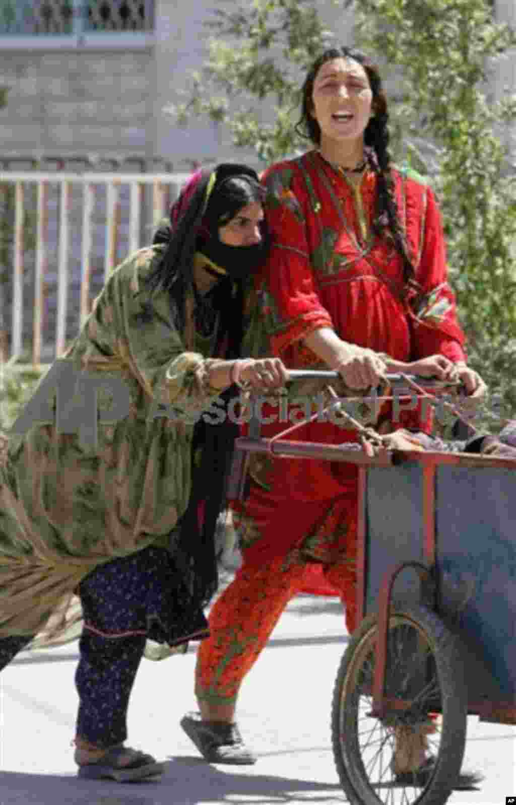 Two gypsy women push a cart in a rich west Amman neighborhood Thursday March 29, 2007