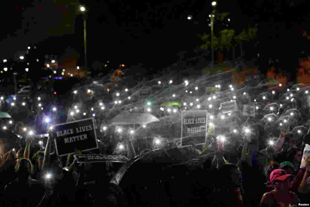 Demonstrators hold up their mobile phones as they continue to protest for a fourth day after the not guilty verdict in the murder trial of Jason Stockley, a former St. Louis police officer, charged with the 2011 shooting of Anthony Lamar Smith, who was black, in St. Louis, Missouri, Sept. 18, 2017.
