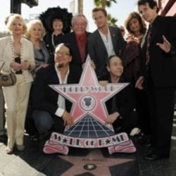A group of celebrities pose in front of the star for legendary illusionist Harry Houdini on the Hollywood Walk of Fame.