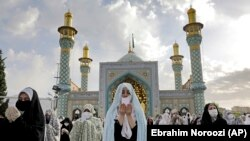 Worshippers wearing protective face masks offer Eid al-Fitr prayers outside a shrine to help prevent the spread of the coronavirus, in Tehran, Iran, Sunday, May 24, 2020