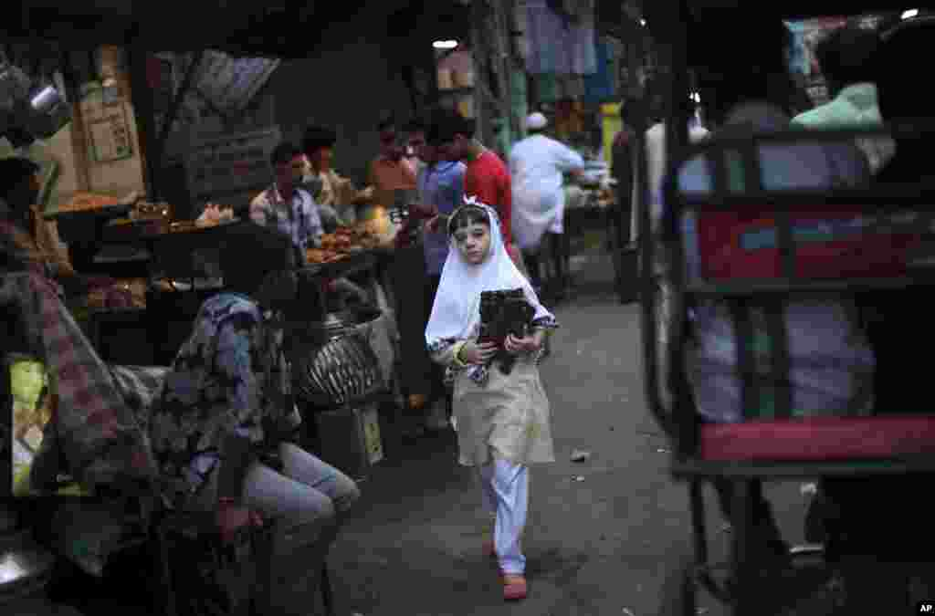 A young Muslim girl walks with a copy of the holy Quran on International Day of the Girl Child in New Delhi, India, October 11, 2012.
