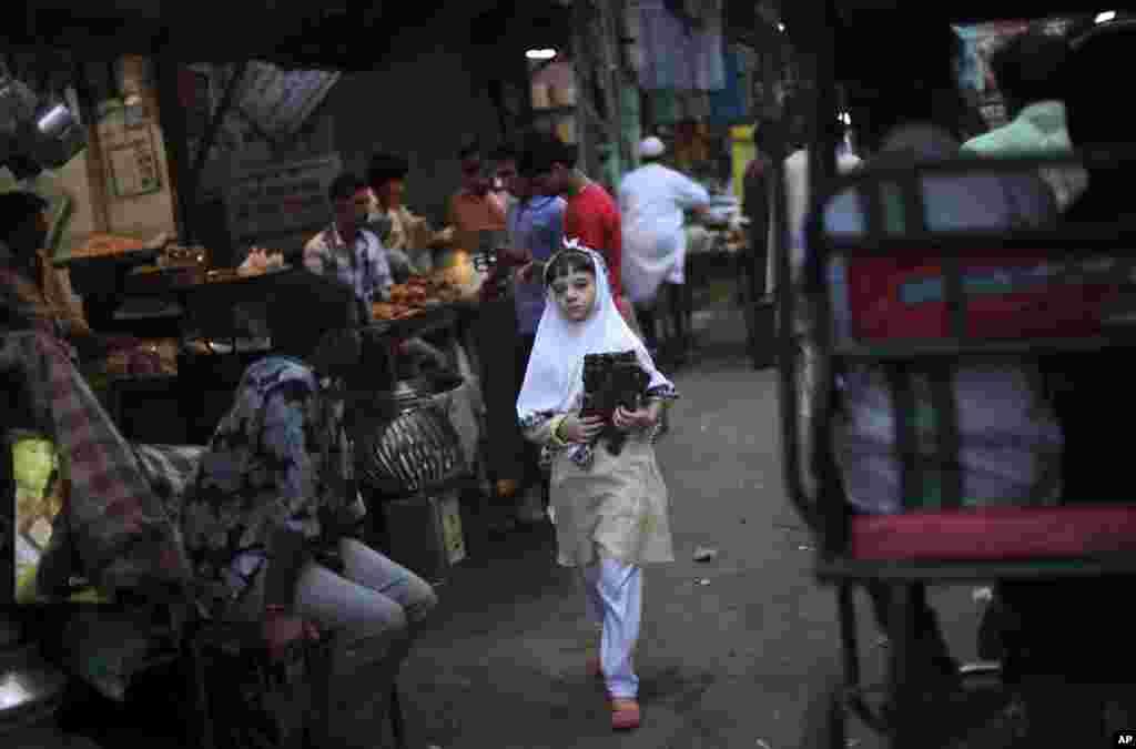 11일 세계 여자아이의 날에 코란을 들고 걸어가는 인도 델리의 무슬림 소녀.