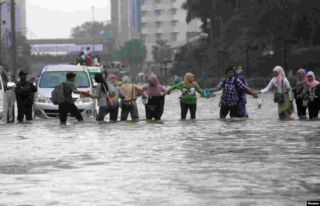 Workers cross a flooded street in the business district in Jakarta, Indonesia, January 17, 2013.