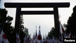 "FILE - Members of nationalist movement ""Ganbare Nippon"" raise Japanese national flags towards the huge Torii gate at the Yasukuni shrine."