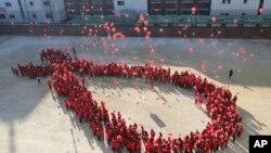 Journée mondiale de lutte contre le VIH Sida : des étudiants sud-coréens forment un ruban rouge, Séoul, le 29 novembre 2016. (AP Photo/Lee Jin-man)