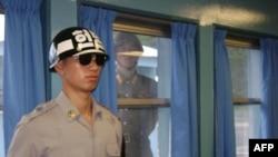 Binh sĩ Bắc Triều Tiên đứng sau cửa sổ trong lúc binh sĩ Nam Triều Tiên (trước) canh gác trong chuyến thăm của Ngoại trưởng Mỹ Hillary Clinton đến làng đình chiến Bàn Môn Ðiếm, ngày 21/7/2010