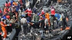 Tim penyelamat mencari korban dari puing-puing kapal feri yang terbakar di lepas pantai Jakarta setelah kapal itu berlabuh di Muara Angke Pelabuhan di Jakarta, Indonesia, Minggu, 1 Januari, 2017. (AP Photo/Rhana Ananda)