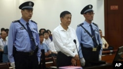 FILE - Bo Xilai, center, in court on charges of bribery, embezzlement and abuse of power in a case set in motion by his wife's murder of a British businessman.