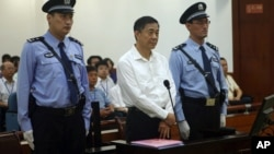 The Chinese court said it will deliver a verdict on Sept. 22 for Bo Xilai, center, on charges of bribery, embezzlement and abuse of power in a case set in motion by his wife's murder of a British businessman, (File photo)..
